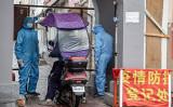5月22日、吉林省吉林市内の集合住宅の出入り口で、市の職員らは防護服を着て住民の身分証明書をチェックし検温を行っていた(STR/AFP via Getty Images)
