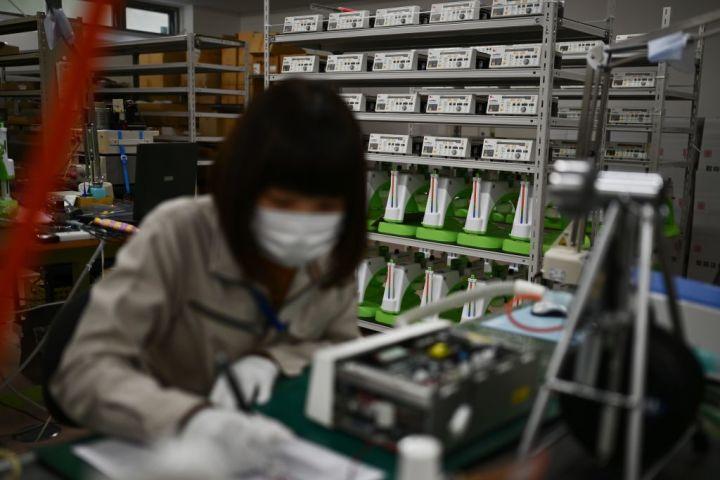 福島県福島市にある医療機器メーカー・コーケン社の作業場で、従業員が機器の最終検査をしている。2020年4月撮影(GettyImages)