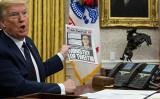5月28日、「オンラインの検閲を阻止する大統領令」に署名するトランプ大統領。手に持つのはニューヨーク・ポストの記事で、Twitterの事実確認責任者がトランプ政権に強烈な偏見を持っていたと報道している(Doug Mills-Pool/Getty Images)