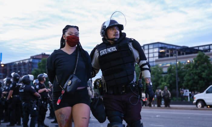 2020年5月31日、米ミネソタ州ミネアポリスでジョージ・フロイド氏の死後に始まった抗議と暴力の6日目の夜に、州知事が発表した午後8時以降の外出禁止令を破って拘束されるデモ参加者(Charlotte Cuthbertson/The Epoch Times)