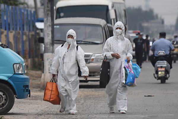 2020年6月13日、北京市食品卸売市場「新発地」の近くを歩く防護服姿の女性市民(GREG BAKER/AFP via Getty Images)