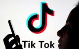 2019年11月7日、スマートフォンを持つ人の後ろに表示されるTikTokのロゴ (Dado Ruvic/Reuters)
