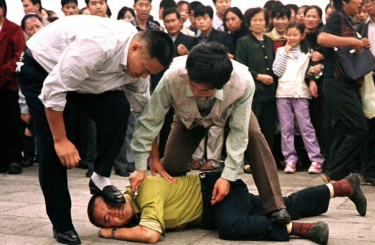 2000年10月1日、天安門広場で法輪功迫害をやめるよう訴えたところ、公安当局者に抑えられ、顔面を踏みつけられた法輪功学習者(AP)