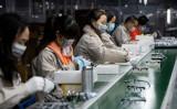 2020年2月28日、中国・温州市にあるアズール眼鏡有限公司で保護マスクを着用しながらメガネフレームを研磨している従業員たち (Noel Celis/AFP via Getty Images)