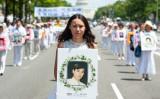 2014年7月17日、法輪功学習者がワシントンDCに集結し、迫害停止を呼びかける集会とパレードを行った。中国共産党の迫害によって死亡した法輪功学習者の写真を手に持つ女性(Larry Dye /The Epoch Times)