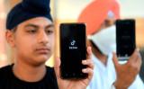 男性が提示するスマートフォンの画面に映し出されたTikTokのロゴ、インドのデリーで撮影(GettyImages)