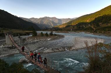 2019年12月6日に撮影された写真は、ブータンのプナカ県にあるプナツァンチュ川にかかる吊り橋の上を歩く観光客の姿(LILLIAN SUWANRUMPHA/AFP via Getty Images)