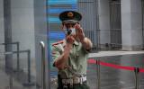 北京のオーストラリア大使館で撮影クルーに手をかざす警備員、2020年8月撮影(GettyImages)