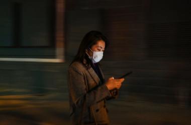 2020年3月17日、中国の上海でスマホをチェックする女性 (HECTOR RETAMAL/AFP via Getty Images)