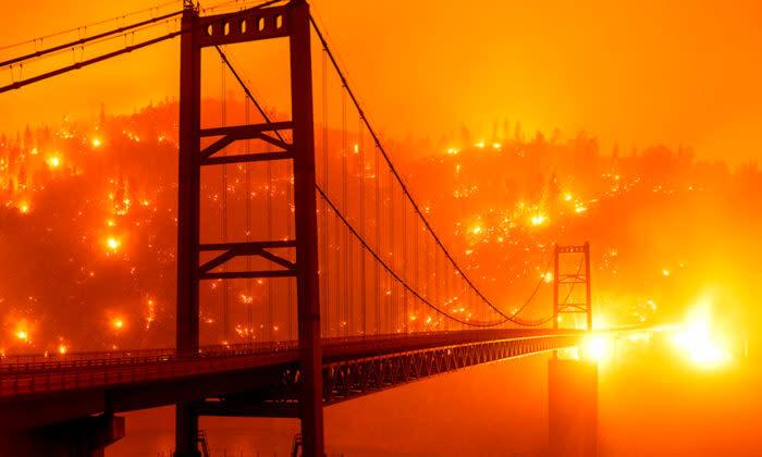 9月9日(水)カリフォルニア州オーロビルの山火事がビッドウェルバーブリッジ後方の丘の斜面を燃やす様子をスローシャッタースピードで撮影(Noah Berger/AP)