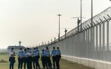 香港の活動家ら12人が収監されている。家族の抗議活動を受けて政府航空関係施設を警備する警察官(GettyImages)