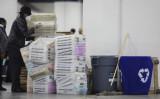 2020年11月4日、ミシガン州デトロイトのTCFセンターで、不在者投票が終わりに近づき、不在者投票の整理に使った空の箱を積むデトロイト選挙局の職員(Elaine Cromie/Getty Images)