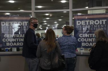 2020年11月4日、デトロイトのTCFセンターの中央集計所で、集計所内で監視員の数が上限に達したと知らされた後、窓越しに開票の様子を見る選挙監視員たち(Elaine Cromie/Getty Images)