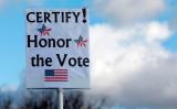 ジョージア州を起訴したパウエル弁護士は、大統領選の現在の結果の無効化を主張した。11月23日、ミシガン州で行われた大統領選の関連運動で、参加者が掲げたメッセージボード(JEFF KOWALSKY/AFP via Getty Images)