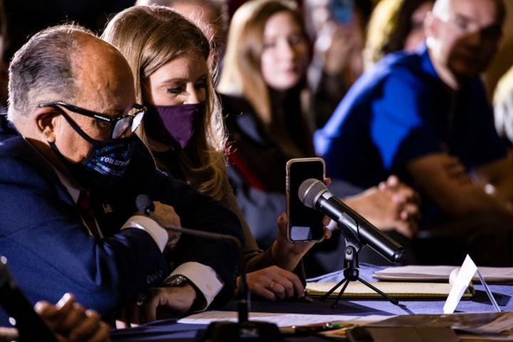 米トランプ陣営の上級法務顧問ジェナ・エリス(Jenna Ellis)氏は11月25日、ペンシルベニア州での記者会見でマイクに携帯電話を向けて、トランプ大統領からの電話音声を伝えている(Samuel Corum/Getty Images)