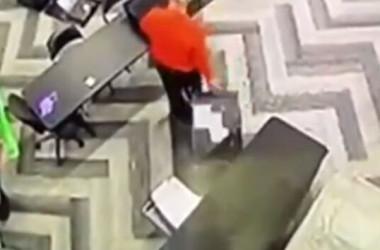 2020年11月3日の夜、選挙監視員不在の間に、票が入っているとされるスーツケースをテーブルの下から持ち出す男性(NTD screenshot)
