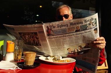 オーストラリアのシドニーで、シドニー・モーニング・ヘラルド紙を読む読者=2012年6月20日(Cameron Spencer/Getty Images)