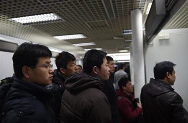 北京市の労働市場で求人情報をチェックしている人々(GREG BAKER / AFP)