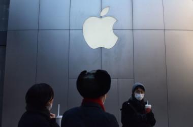 2018年12月11日、中国北京のアップルストアの前を通り過ぎる人々(GREG G BAKER/AFP/GettyImages)