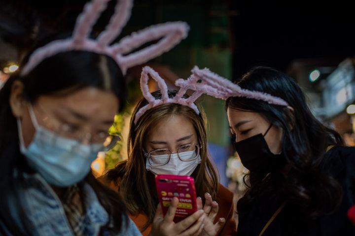 2020年10月、携帯電話を覗き込む女性たち。北京で撮影(NICOLAS ASFOURI/AFP via Getty Images)