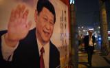 北京で開かれた第19回共産党大会が閉幕した後、中国の習近平国家主席の道端のポスターを通り過ぎる男性=2017年10月24日(GREG BAKER/AFP via Getty Images)