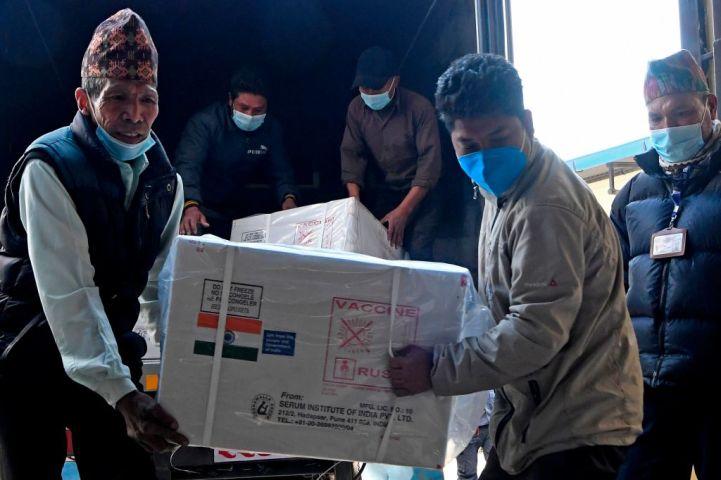2021年1月21日、インドから無償提供された新型コロナウイルスワクチンの梱包箱を積み下ろすネパールのカトマンズ公衆衛生局スタッフ(RAKASH MATHEMA/AFP via Getty Images)