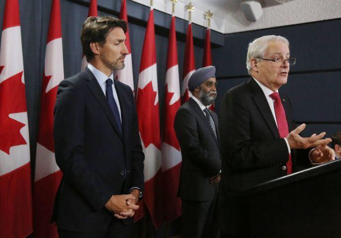 2020年1月、カナダ政府施設内で開かれた記者会見で発言するマーク・ガルノー運輸大臣(当時)。カナダのジャスティン・トルドー首相とハルジット・サジャン国防相は両脇に立つ(DAVE CHAN/AFP via Getty Images)