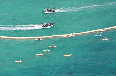 沖縄米軍基地移設により、名護市辺野古の埋め立て工事が行われている。工事に抗議する人々がカヌーに乗り、抗議現場に接近する。海上保安庁のゴムボートが巡視する(JIJI PRESS/AFP via Getty Images)