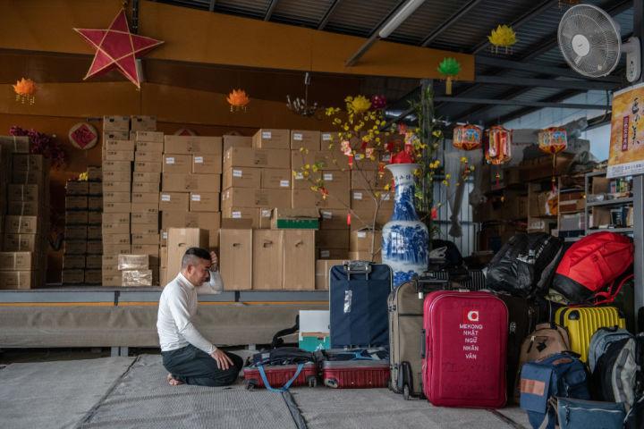 写真は荷物を整理するベトナム人労働者(Photo by Carl Court/Getty Images)