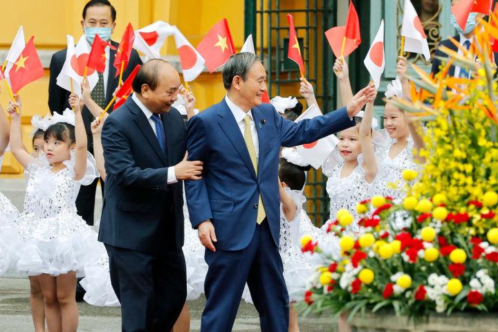 ベトナムで歓迎を受ける菅首相(Photo by MINH HOANG/POOL/AFP via Getty Images)