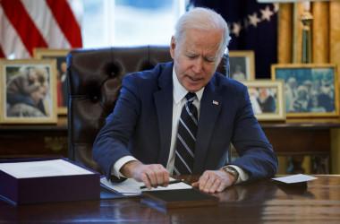 ホワイトハウス内の大統領執務室で1.9兆ドル(約200兆円)規模の追加経済支援策「米国救済計画」法案に署名するジョー・バイデン大統領=2021年3月11日(Tom Brenner/Reuters)