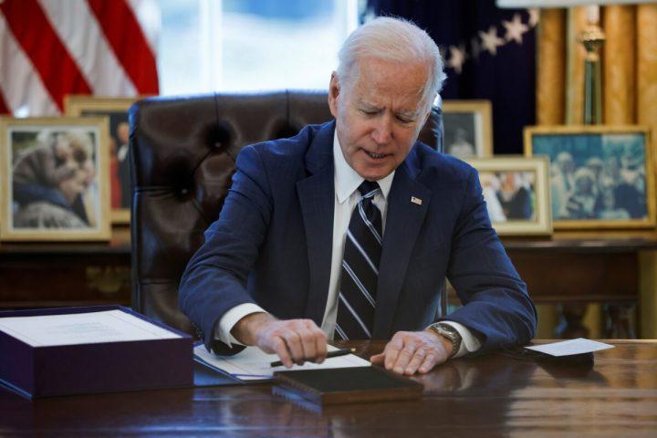 ホワイトハウス内の大統領執務室で「アメリカ救済計画」に署名するジョー・バイデン大統領=2021年3月11日