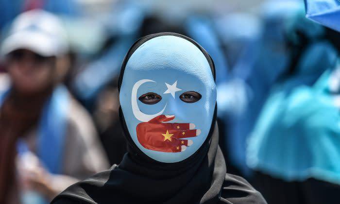 2018年7月5日、イスタンブールの中国領事館前で、中国のイスラム人迫害を非難するデモ参加者。この人のマスクは東トルキスタン (一部のウイグル人分離主義者は新疆ウイグル自治区をこう呼ぶ) の旗のデザインで、口は中国国旗の色をした手で覆われている(OZAN KOSE/AFP/Getty Images)