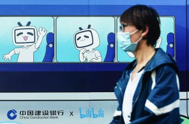 2021年3月29日、中国浙江省杭州市で、動画配信サイト「Bilibili」のマスコットやロゴの画像の前を歩く歩行者。(STR/AFP via Getty Images)
