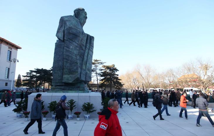 北京の中国国家博物館前に設置された孔子のブロンズ像の前を通る人々。2011年1月撮影(STR/AFP via Getty Images)