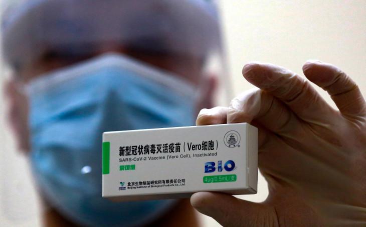 2021年1月13日、ヨルダンの首都アンマンにある予防接種センターで、新型コロナウイルス(COVID-19)感染症に対する中国シノファーム製ワクチンを掲げる医療従事者(KHALIL MAZRAAWI/AFP via Getty Images)
