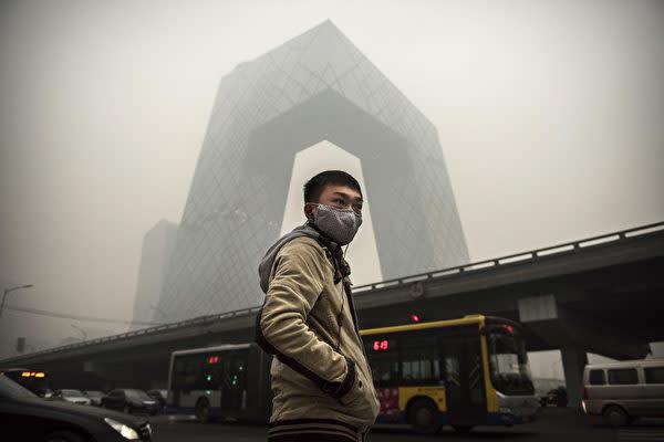 2014年11月、大気汚染が発生した北京市で中国国営中央テレビ本社の近くにいるマスク姿の男性(Kevin Frayer/Getty Images)