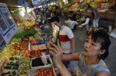 中国でスマホアプリを利用して青果品を購入する女性(WANG ZHAO/AFP via Getty Images)
