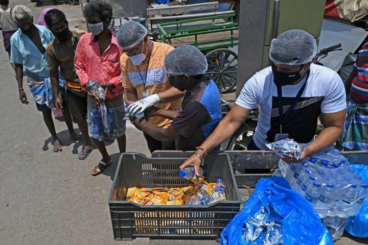 食料と水を配布するボランティアとそれを受け取る民衆。5月26日、タミル・ナードゥ州にて撮影(Photo by ARUN SANKAR/AFP via Getty Images)