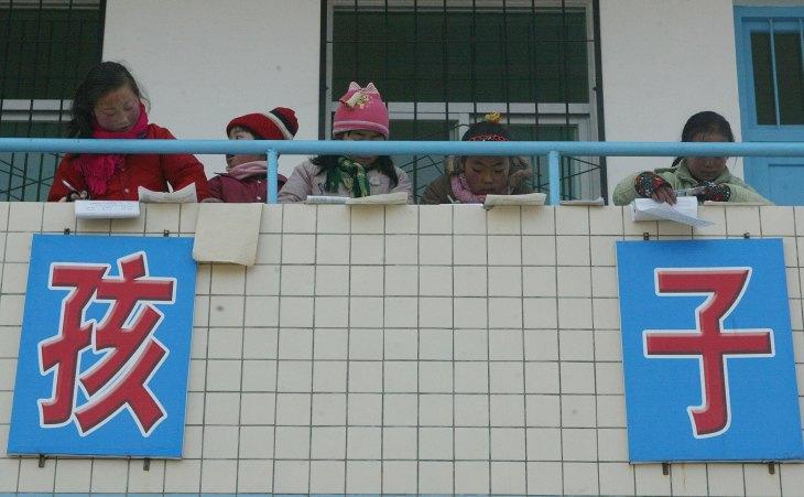 中国陝西省春華県城関郷にある田舎の学校で、放課後に教室のバルコニーで宿題をする子供たち(China Photos/Getty Images)