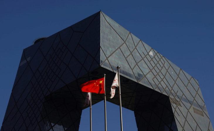 中国・北京にある中国国営CCTVとその外国語放送チャンネルCGTNの本拠地であるCCTV本部ビルの外には、中国の国旗がはためいている=2021年2月5日(Carlos Garcia Rawlins via Reuters)