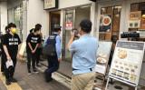 会場になった建物内に駆け込む警察官。7月1日、東京都内にて撮影(王文亮/大紀元)