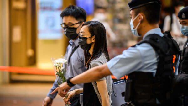 香港警察は、警察官を刺した後に自殺した男性を追悼しないよう市民に警告した。2021年7月2日、事件の現場では、警察は白い花を持つ人々を止めてチェックしている(ANTHONY WALLACE/AFP via Getty Images)