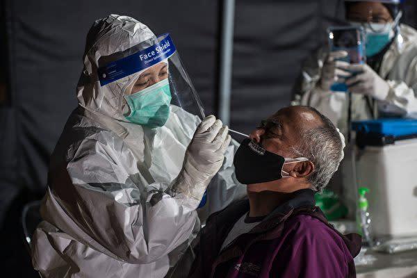2020年12月31日、インドネシア・スラバヤで医療従事者が市民にPCR検査を行っている(JUNI KRISWANTO/AFP via Getty Images)