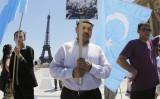 2010年7月4日、パリのエッフェル塔前でプラカードを掲げるウイグル人男性。参考写真(FRANCOIS GUILLOT/AFP via Getty Images)