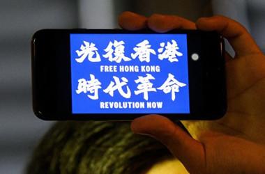2019年8月23日、「光復香港、時代革命(香港を取り戻せ、時代の革命だ)」と書かれた携帯を手に持つ香港の抗議者(ANTHONY WALLACE/AFP/Getty Images)