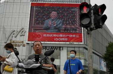 2021年7月1日に北京で行われた中国共産党創立100周年記念式典で、習近平国家主席が演説する様子を映した大型スクリーンの前を歩く人々(Noel Celis/AFP via Getty Images)