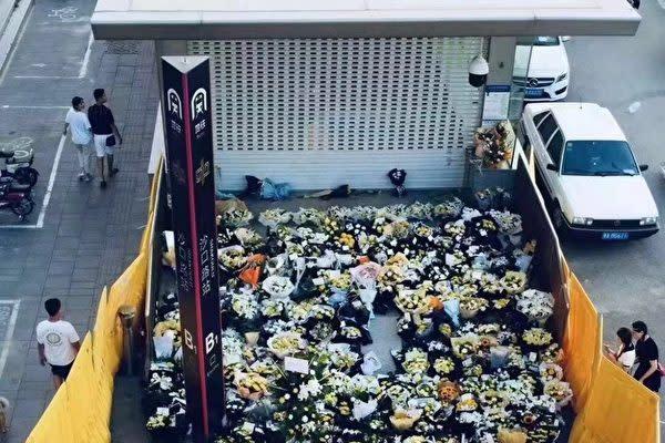 鄭州市地下鉄出口で、多くの市民が献花したが、当局はフェンスを設置した(微博)