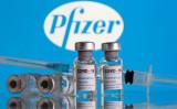 新型コロナワクチンのラベルが貼られた薬剤と注射器。後ろはファイザー社のロゴ (Dado Ruvic/Reuters)