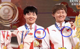 中国国営テレビ放送(CCTV)は、IOCが中国選手2人が表彰式で毛沢東バッジを着用した問題を調査し始めたのを受けて、同表彰式の映像を編集した(スクリーンショット)